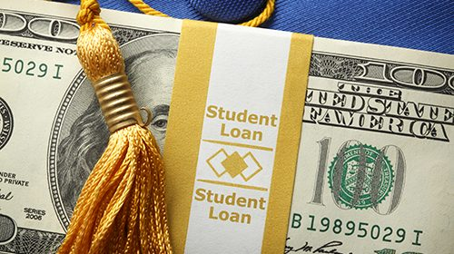 "A stack of one hundred dollar bills in a money wrapper labeled ""Student Loan"" on top of a blue graduation cap.  A gold graduation tassel is draped over the stack of money."