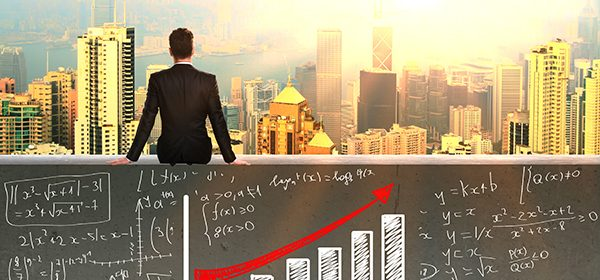 Financial growth concept with businessman sitting on concrete wall with business graphs and formulas and looking at cityscape with sunlight
