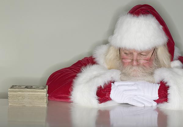 Santa Claus looking at stack of money