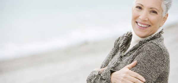 A senior woman on a beach looking happy