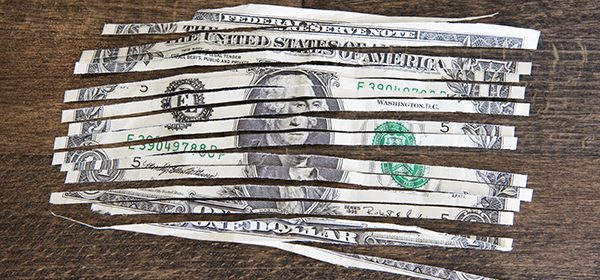 A shredded one dollar note on a wooden table