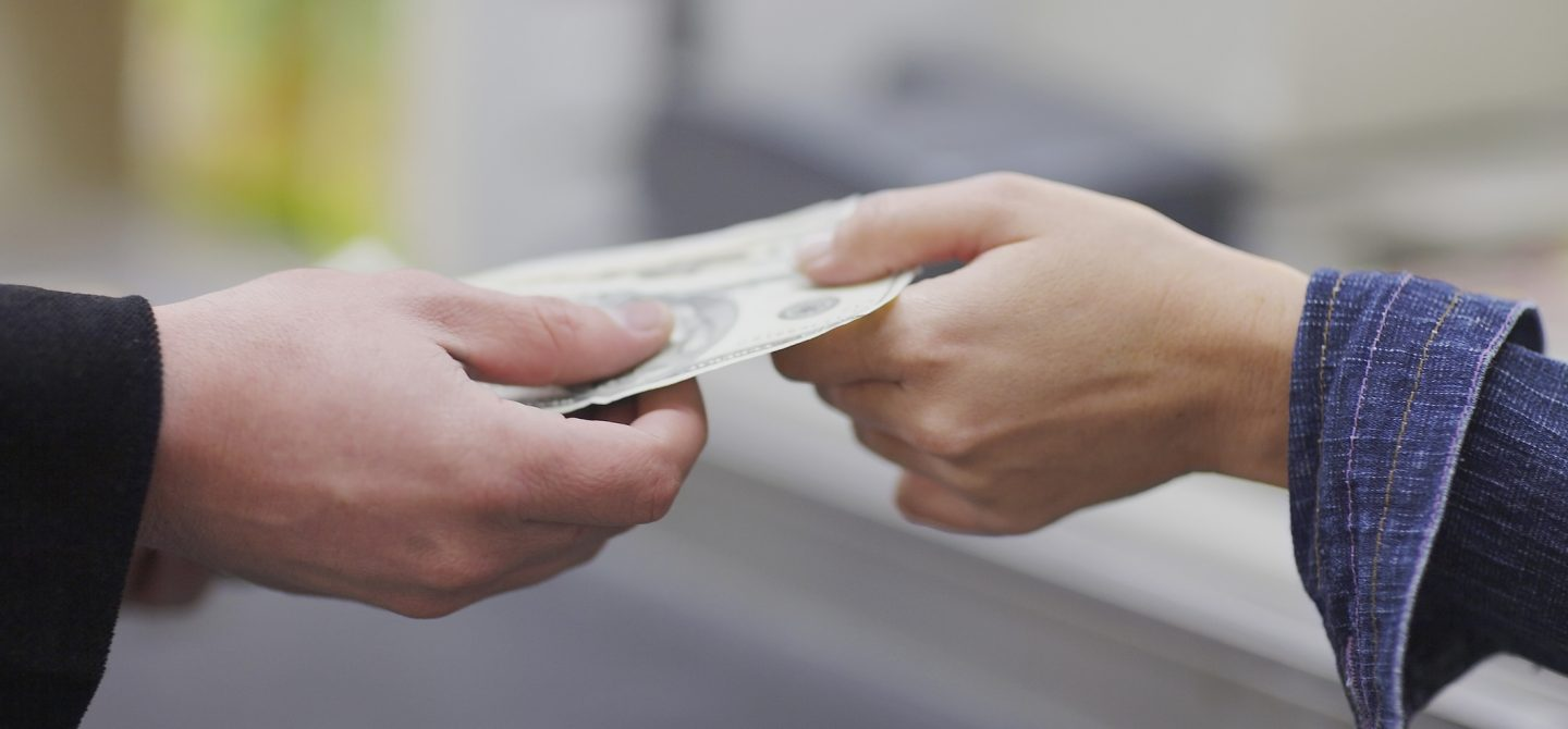 People's hands exchanging paper currency