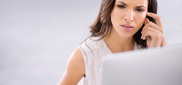 Young woman looks at computer with confused expression.
